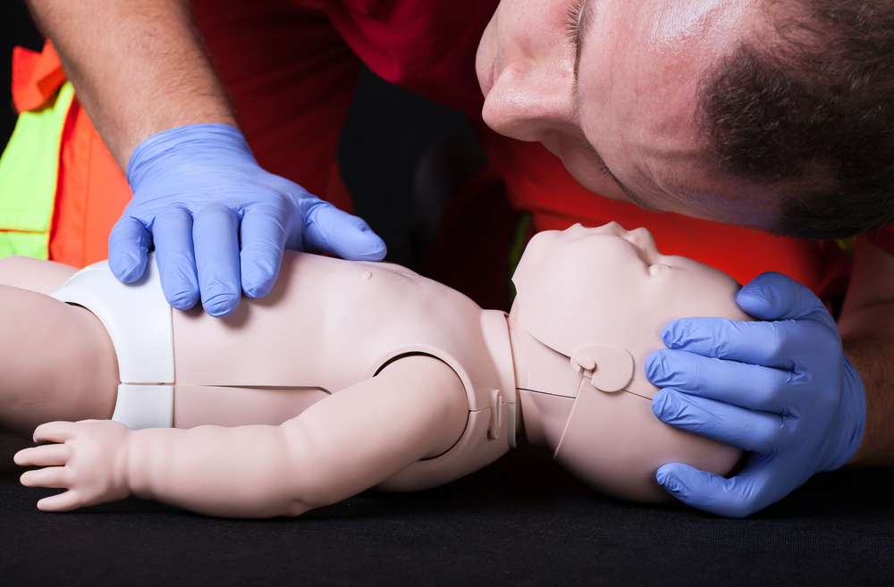 Paramedic demonstrating life function check on infant dummy